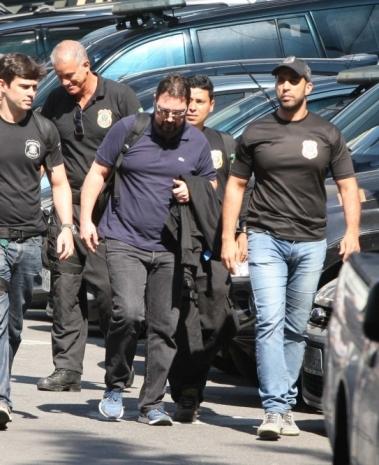 Alexandre Pinto, de azul, sendo levado por agentes da PF, em agosto
