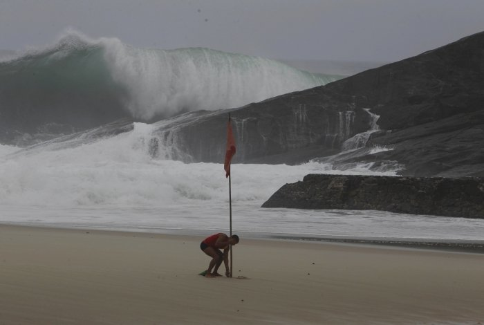 Salva-vidas finca bandeira vermelha em dia de ressaca na praia do Leblon.