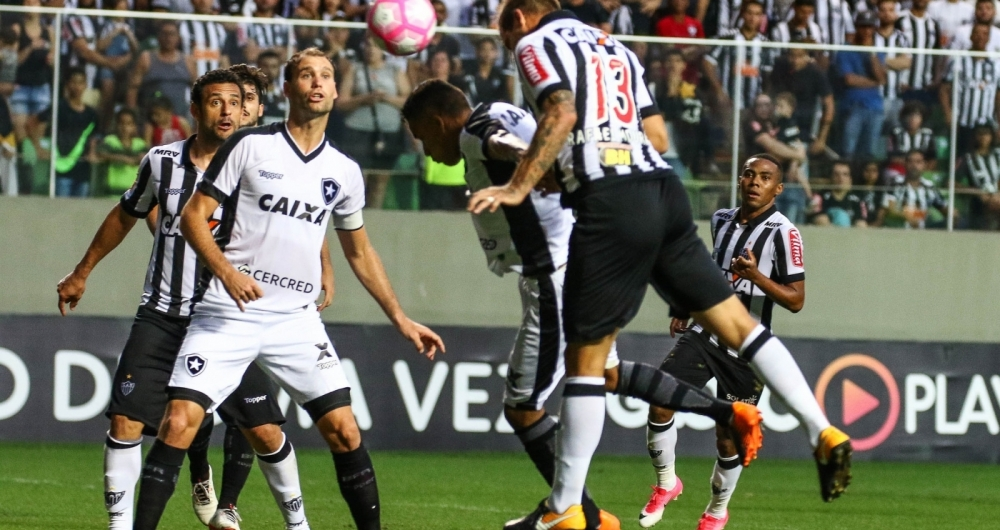 Rafael Moura disputa a bola com Arnaldo: a defesa do Botafogo resistiu bem � press�o no Independ�ncia