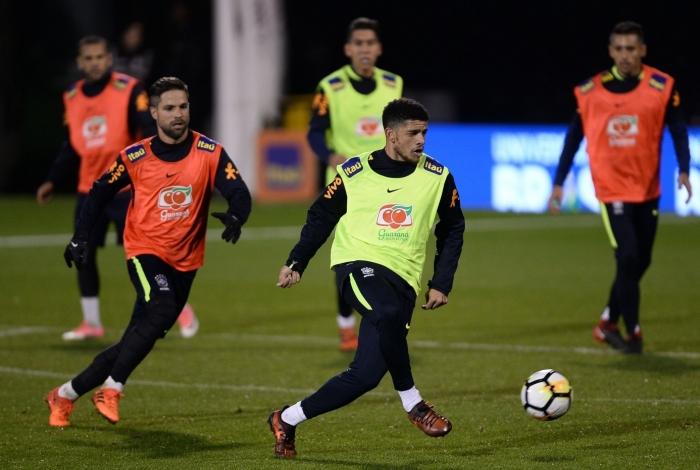 Diego (E) tenta chegar na marcação a Taison: meia treinou em Londres