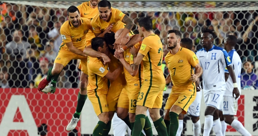 Australia's Mile Jedinak (C) is mobbed by his teammates after scoring against Honduras during their 2018 World Cup qualification play-off football match at Stadium Australia in Sydney on November 15, 2017. / AFP PHOTO / William WEST / -- IMAGE RESTRICTED TO EDITORIAL USE - STRICTLY NO COMMERCIAL USE --