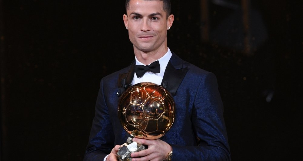 This handout photo released on December 7, 2017 by L'Equipe shows Portugese player Cristiano Ronaldo posing with the 2017 Ballon d'Or France Football trophy in Paris.