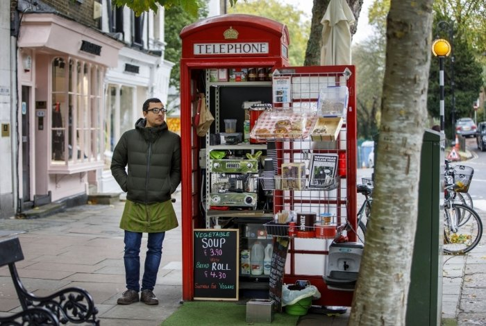 Umar Khalid poses outside the red telephone box from which he runs a coffee shop in Hampstead Heath, north London on October 20, 2017. Facing extinction due to ubiquitous mobile phones, Britain's classic red telephone boxes are being saved from death row by ingenious conversions into all sorts of new uses. / AFP PHOTO / Tolga Akmen / TO GO WITH AFP STORY 'Britain-heritage-business' by Martine PAUWELS