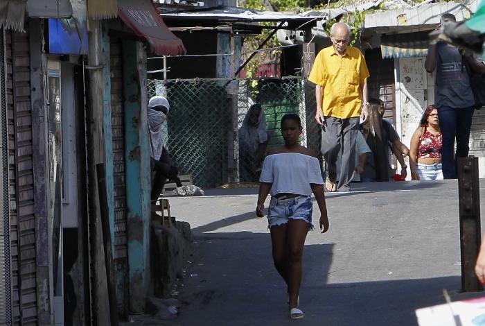 Bandido esconde o rosto e mostra a arma pronta para atirar em PMs no Jacarezinho. Atrás de parede marcada por tiros, ao lado de pedestres e barricadas