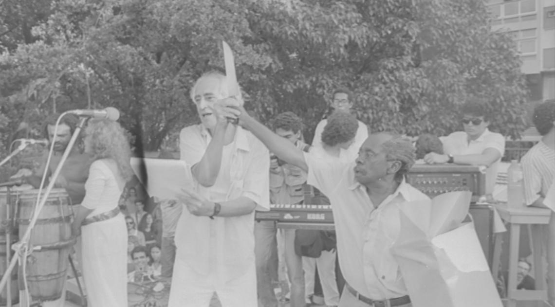 José Celso Martinez Corrêa e Grande Otelo fazem uma representação com uma faca, arma que há 30 anos foi usada no assassinato do ator e diretor Luiz Antonio Martinez Corrêa, irmão de Zé Celso. O crime aconteceu no dia 23 de dezembro de 1987, e no dia 30, dia da foto, artistas, amigos e parentes participaram de uma missa campal na Praça Nossa Senhora da Paz, em Ipanema.