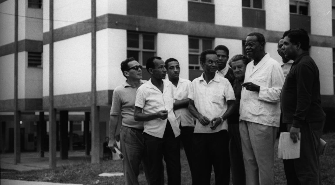 Pixinguinha, um dos maiores compositores brasileiros, sorri ao lado de camaradas seus no conjunto residencial construído pela Ordem dos Músicos, em Inhaúma, onde passou a viver em 1970 (foto é de agosto de 1971). Com cigarro na mão, ele veste a camisa de pijama, um de suas roupas preferidas. Deixara a casa em que morava, em Ramos, na Rua Belarmino Barreto, que hoje leva seu nome.
