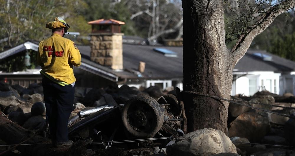Um bombeiro busca por sobreviventes em meio aos escombros, após deslizamentos que deixaram 20 mortos na Califórnia