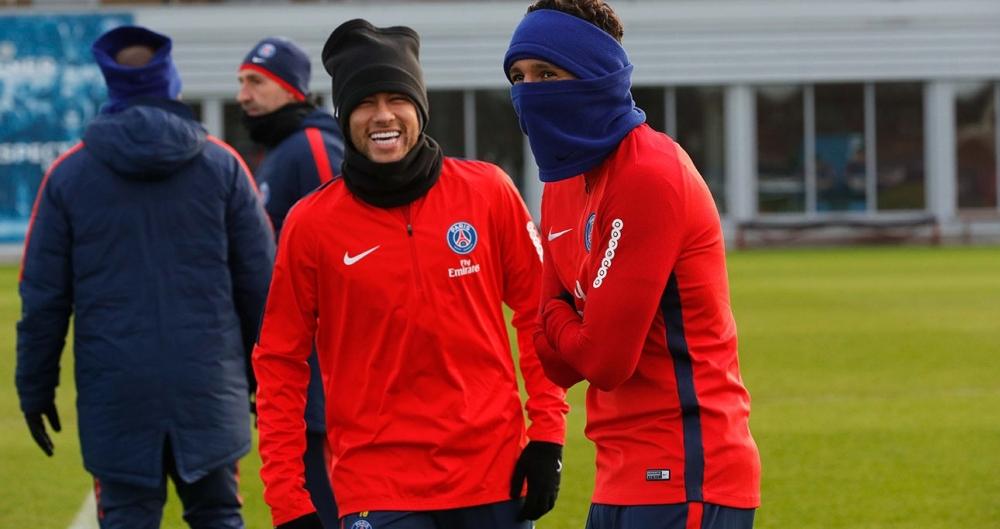 Neymar (E) e Marquinho tentam espantar o frio no treino do PSG