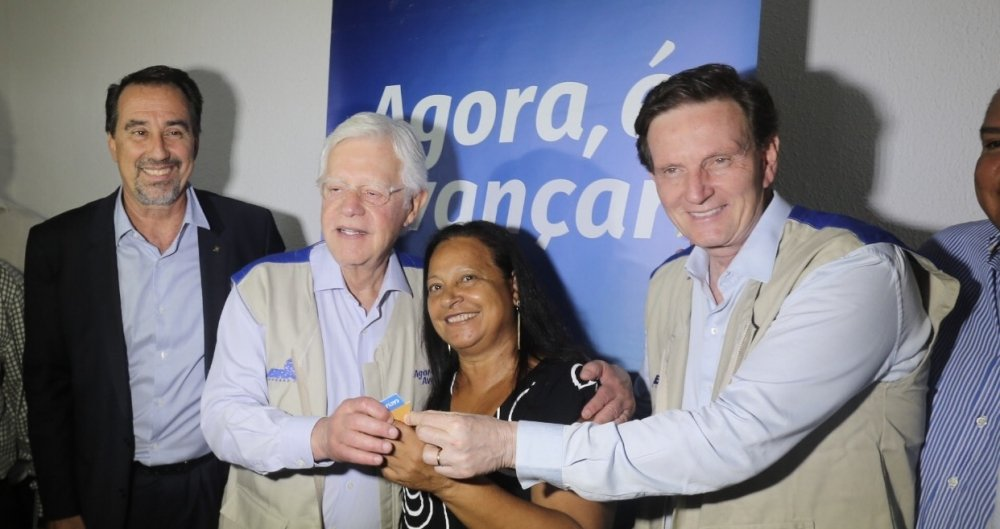 Crivella entrega a chave a uma beneficiada pelo Minha Casa Minha Vida. Ao lado do presidente da Caixa, Gilberto Occhi, e o ministro Moreira Franco