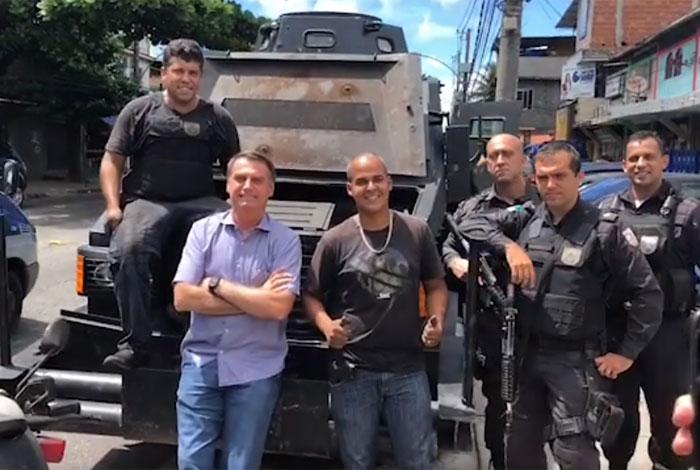 Bolsonaro posa com policiais na Cidade de Deus em frente a um