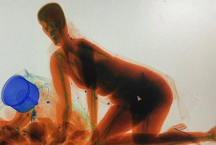 Silhueta da chinesa passando na esteira de raio x