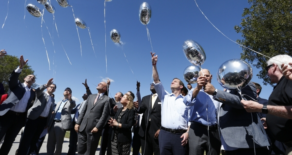 City, county and state officials release balloons in honor of the victims during a prayer vigil for the Marjory Stoneman Douglas High School shooting at Parkridge Church in Coral Springs, Florida on February 15, 2018.  The heavily armed teenager who gunned down students and adults at a Florida high school was charged Thursday with 17 counts of premeditated murder, court documents showed.Nikolas Cruz, 19, killed fifteen people in a hail of gunfire at Marjory Stoneman Douglas High School in Parkland, Florida. Two others died of their wounds later in hospital, the sheriff's office said.  / AFP PHOTO / RHONA WISE       Caption