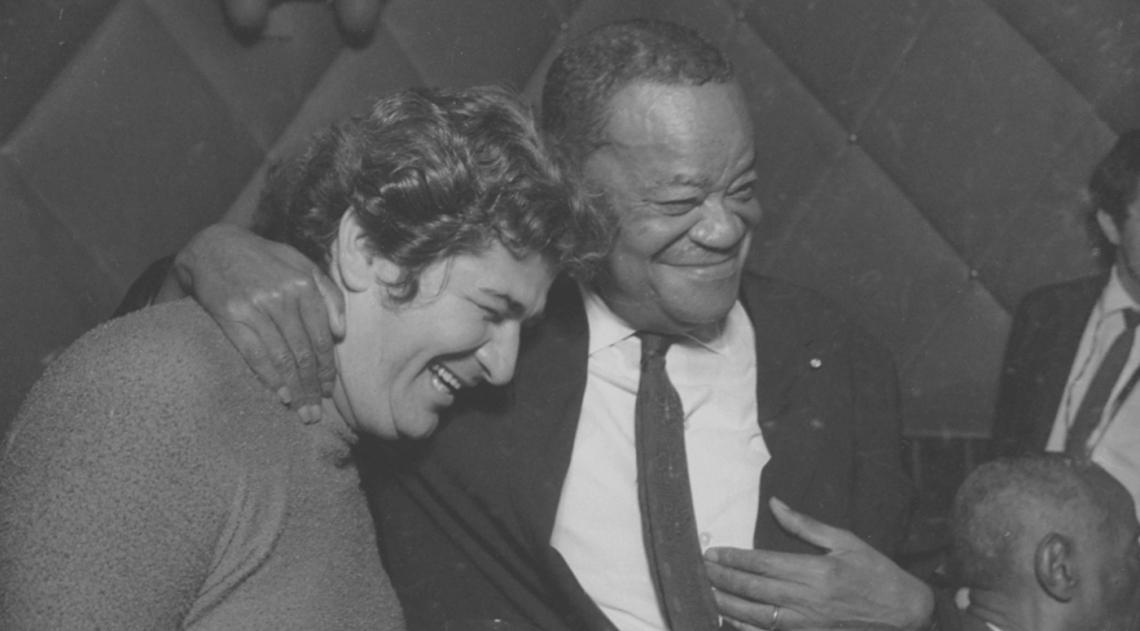 Pixinguinha, de terno, sorri na comemora��o de seu anivers�rio no Bar (ou Whiskeria) Gouveia, na Travessa do Ouvidor, no Centro, em 1968. O espa�o era frequentado assiduamente pelo maestro e m�sico genial, que tinha cadeira cativa e sempre pedia u�sque com gelo e soda; Pixinguinha conheceu o local em 1953 e o frequentou at� �s v�speras de sua morte, em 17 de fevereiro de 1973, h� exatos 45 anos.
