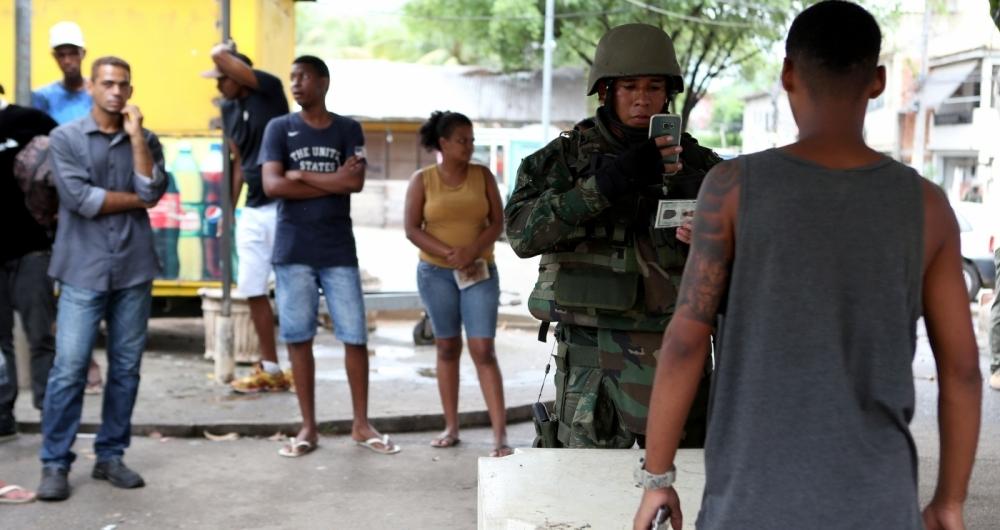 Fuzileiros navais identificam moradores da Vila Kennedy, fotografando o documento de identidade e o rosto durante a operação