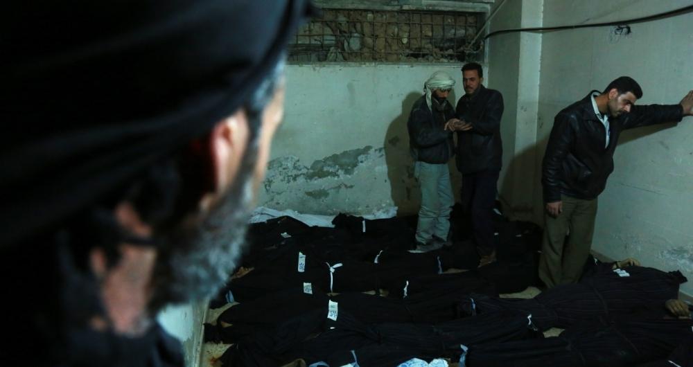 Sírios tentam identificar corpos em hospital de Douma, após bombardeios do governo sírio na região rebelde de Ghouta Oriental.