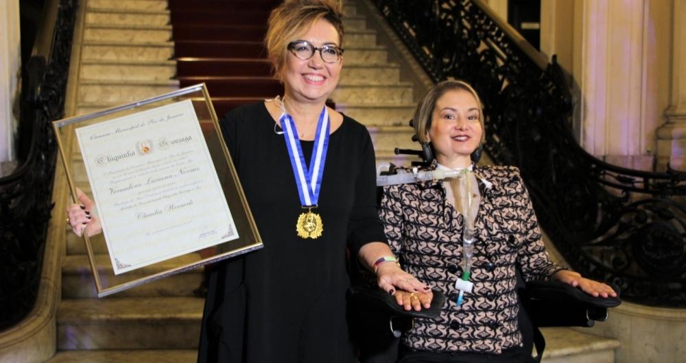 Claudia Werneck exibe a medalha ao lado da vereadora Luciana Novaes
