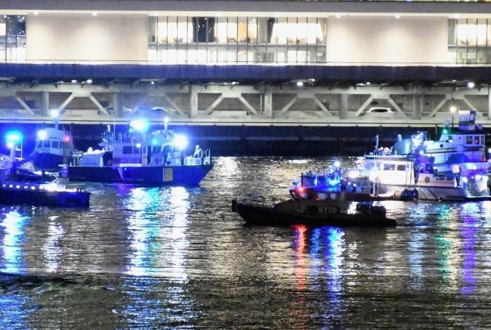 Agentes trabalham no local onde um helicóptero caiu no East River em Nova Iorque.