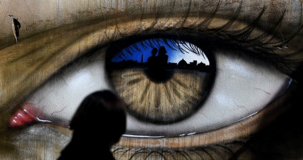Em Roma, uma garota passa por uma obra pintada pelo artista de rua brit�nico My Dog Sighs, famoso por retratar olhos em lugares p�blicos