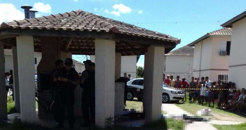 Moradores observam os corpos e policiais fazem a per�cia no local