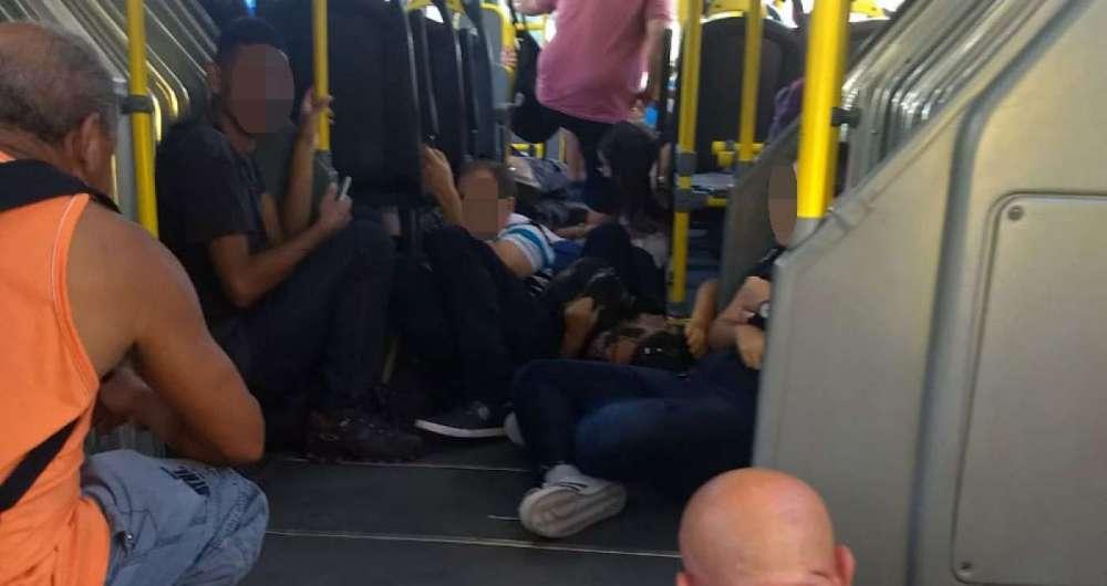 Passageiros de BRT se agacham para se protegerem dos tiros de confronto no Bateau Mouche, na Praça Seca