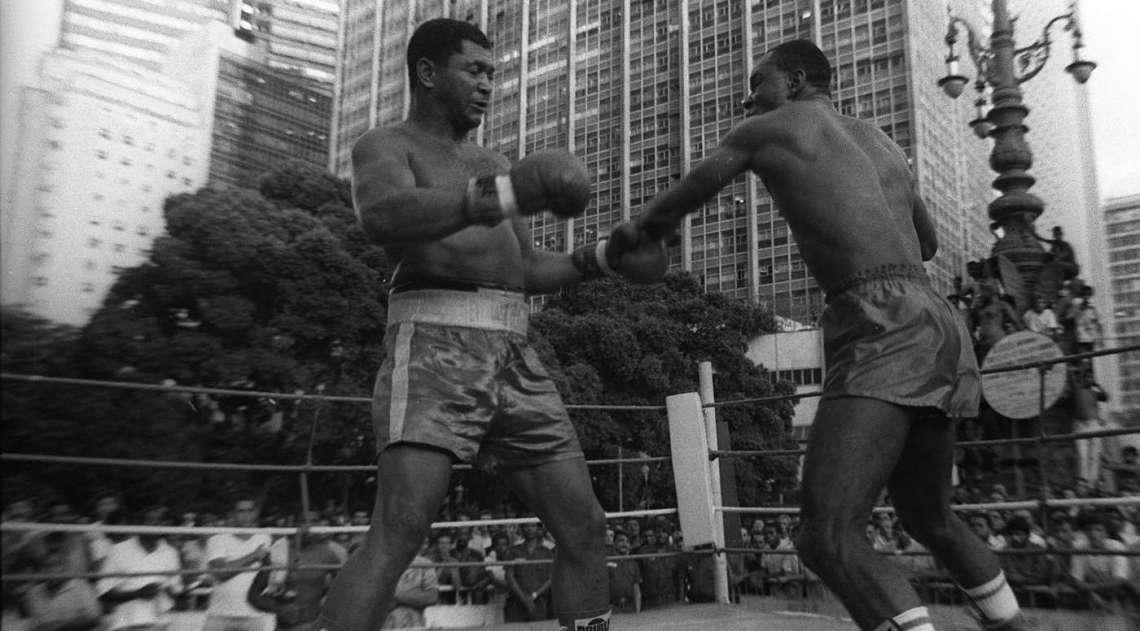 O ringue de pugilismo  foi armado em pleno Largo da Carioca, no Centro do Rio em 2 de mar�o de 1990. Dion�sio Laz�rio , o Bugre, � direita, desafiou, despertou desconfian�a, mas venceu Jos� Augusto da Silva , o Tortinho, na disputa pelo t�tulo estadual de boxe, peso-pesado. Uma multid�o,  acompanhou a peleja promovida pela Sociedade Amigos da Rua da Carioca, Sarca, em comemora��o aos 425 anos do Rio