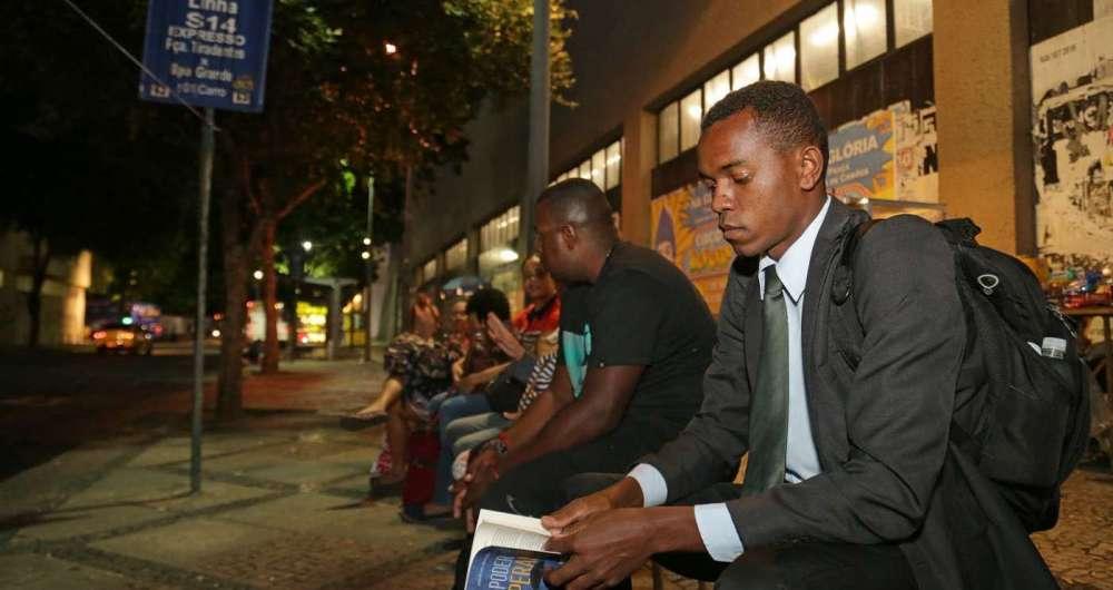 Passageiros, como Robson (livro na mão), dizem ser comum esperar mais de uma hora por um ônibus das linhas 366 e 398 para Campo Grande