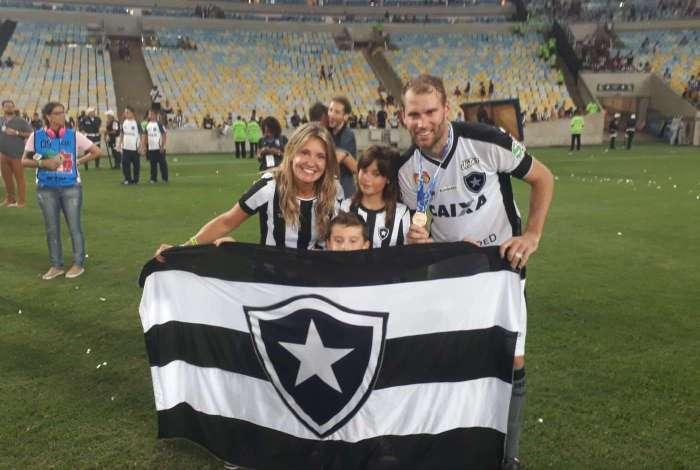 Joel Carli posa com a bandeira do Fogão, ao lado dos filhos e da esposa: volta por cima e volta olímpica
