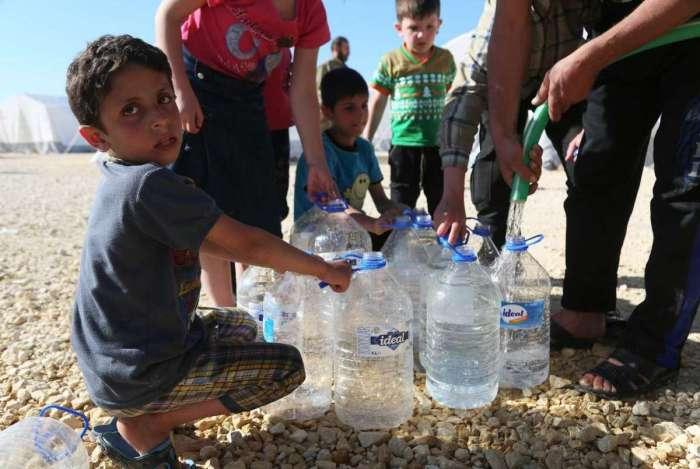 Uma criança se abastece de água em Azaz, um dos muitos campos de refugiados da Síria. Treze milhões de pessoas precisam de ajuda no país