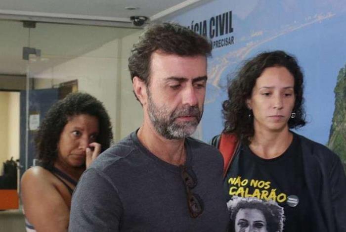 A arquiteta Mônica Benício, viúva de Marielle Franco, é acompanhada pelo deputado estadual Marcelo Freixo no prédio da Chefia da Polícia Civil em encontro sobre investigação do assassinato da vereadora.