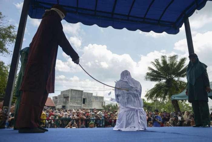 Uma mulher é açoitada publicamente em frente a uma mesquita na capital da província, Banda Aceh.