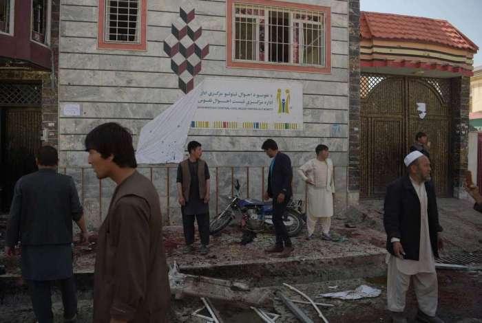 Afeg�os inspecionam o local de um atentado suicida em frente a um centro de registro de eleitores em Cabul.