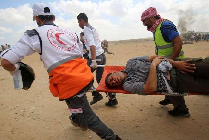 Os palestinos carregam um manifestante ferido durante confrontos com forças israelenses ao longo da fronteira com a Faixa de Gaza