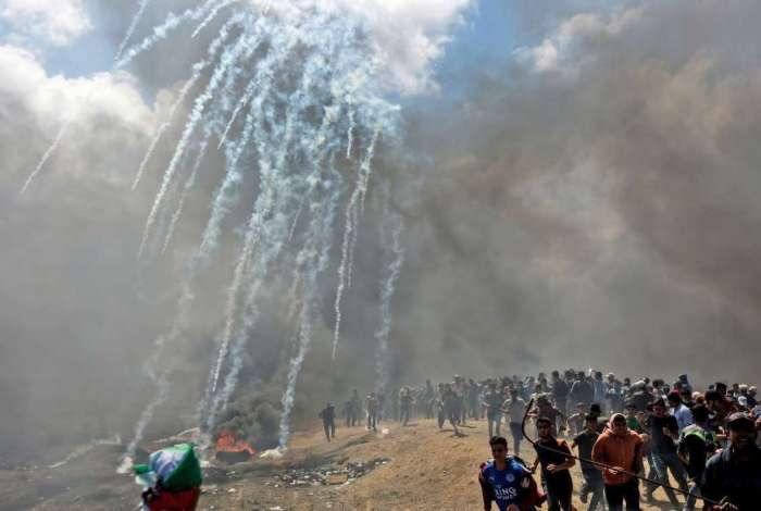 Palestinos fogem de gás lacrimogêneo disparado por forças israelenses perto da fronteira entre a faixa de Gaza e Israel, em 14 de maio