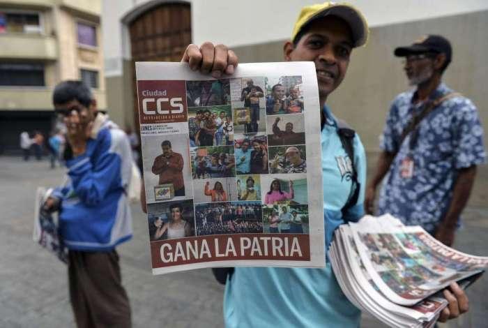 Um vendedor segura um jornal referindo-se � vit�ria do presidente reeleito Nicolas Maduro na elei��o presidencial venezuelana em Caracas