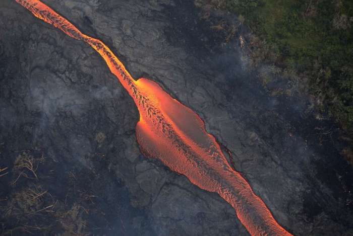 A lava de uma fissura do vulc�o Kilauea passa por �rvores derrubadas em dire��o ao Oceano Pac�fico, na Grande Ilha do Hava�