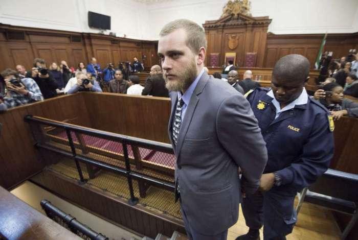 Henri Van Breda é algemado após ter sido condenado por matar seus pais e irmão e atacar sua irmã com um machado em sua casa de luxo em 2015
