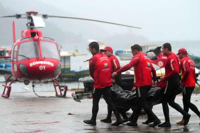 Bombeiros carregam o corpo de uma das vítimas do naufrágio