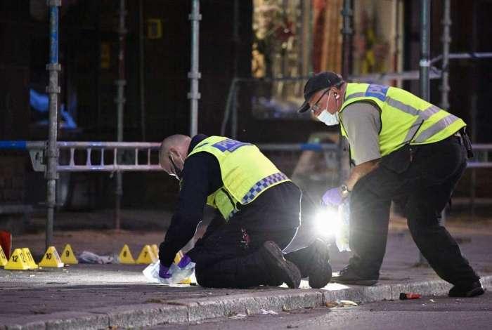 Policiais vasculham a cena do crime depois que cinco pessoas ficaram feridas em um tiroteio no centro da cidade sueca de Malmo