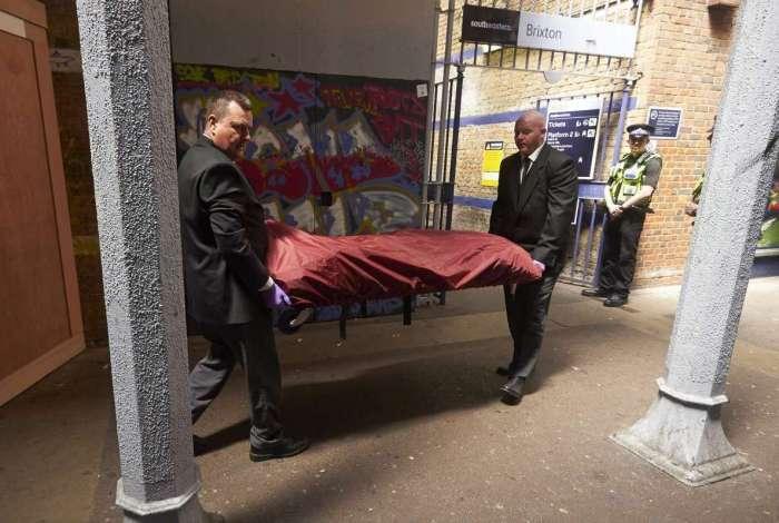 Um corpo � levado em maca da esta��o de trem de Brixton, ap�s um incidente nas linhas ferrovi�rias de Londres, Inglaterra