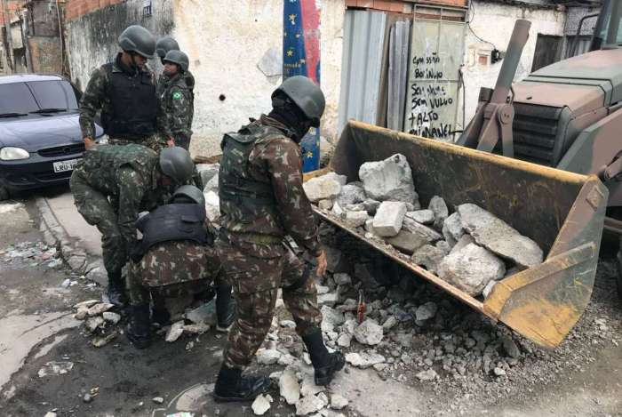 Militares destroem barricadas montadas por traficantes na CDD e usam escavadeira para retirar entulho
