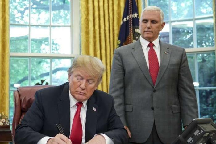 O vice-presidente Mike Pence observa o presidente dos EUA, Donald Trump, assinar uma ordem executiva sobre imigração no Salão Oval da Casa Branca