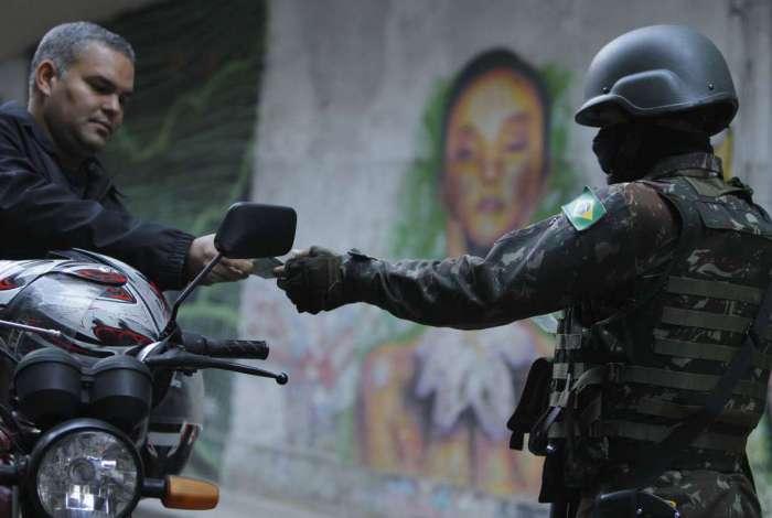 Militar pede documento de motociclista em operação nas favelas do Chapéu Mangueira e Babilônia, no Leme