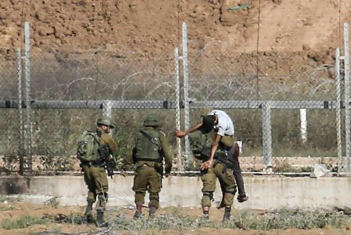 Soldados israelenses carregam um garoto palestino, ferido quando tentava se aproximar da fronteira perto de Jabalia, em Gaza