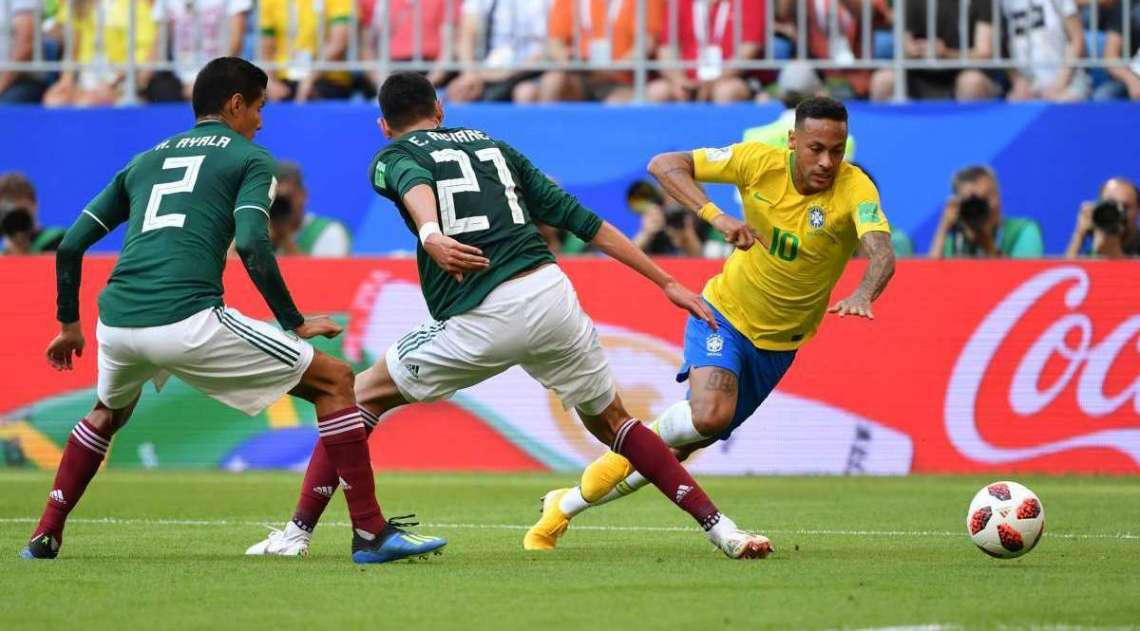 Mexico's defender Edson Alvarez (C) and Brazil's forward Neymar vie for the ball during the Russia 2018 World Cup round of 16 football match between Brazil and Mexico at the Samara Arena in Samara on July 2, 2018. / AFP PHOTO / EMMANUEL DUNAND / RESTRICTED TO EDITORIAL USE - NO MOBILE PUSH ALERTS/DOWNLOADS