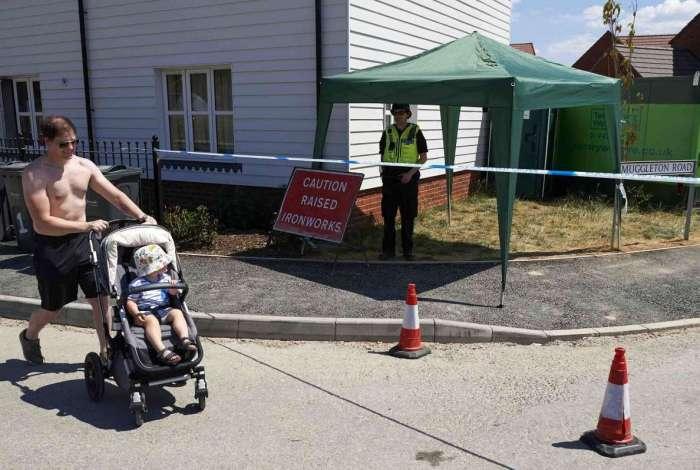Morador passa com bebê diante de guarda em Amesbury, Inglaterra. Polícia tenta identificar fonte da contaminação que matou mulher