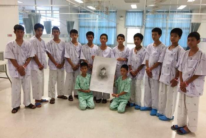 Membros do time de futebol resgatado posam depois de escrever mensagens em um desenho do ex-mergulhador Saman Kunan, que morreu em 6 de julho, durante a missão de resgate