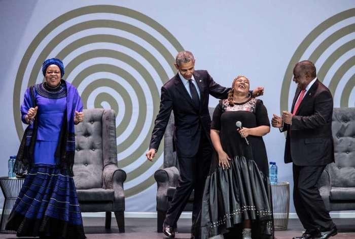 Ex-presidente Obama, viúva de Mandela, Graca Machel, e presidente da África do Sul, Cyril Ramaphosa, dançam durante apresentação da cantora Thandiswa Mazwai (AFP photo/ Marco Longari)