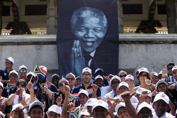Capitão sul-africano da equipe de críquete Faf du Plessis posa com crianças em idade escolar e colegas de equipe em uma cerimônia para marcar o centésimo aniversário de Mandela (AFP photo/ Ishara S. Kodikara)
