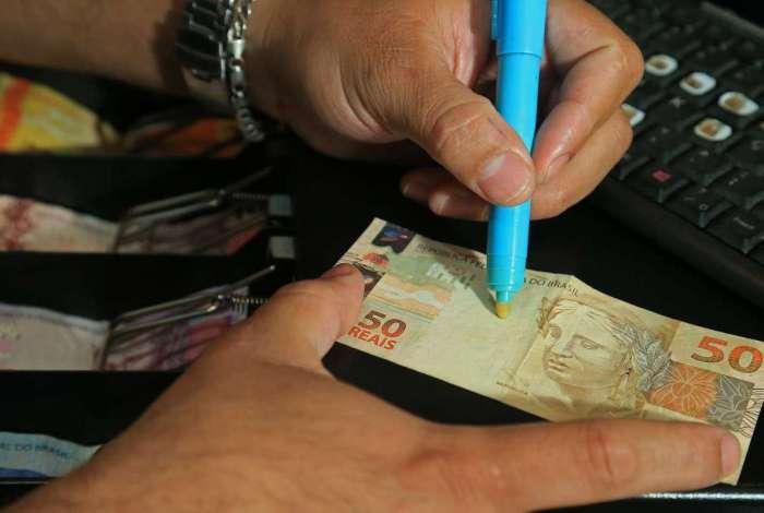 Para evitar o recebimento de dinheiro falsificado, comerciantes utilizam tecnologias como caneta de luz negra e máquinas testa-nota