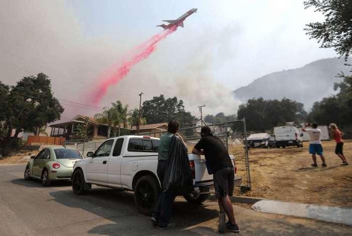 Avião despeja retardador de fogo sobre as chamas de incêndio na Califórnia